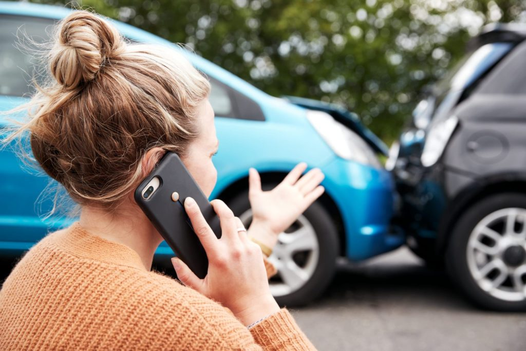 woman on phone with hand up after car accident