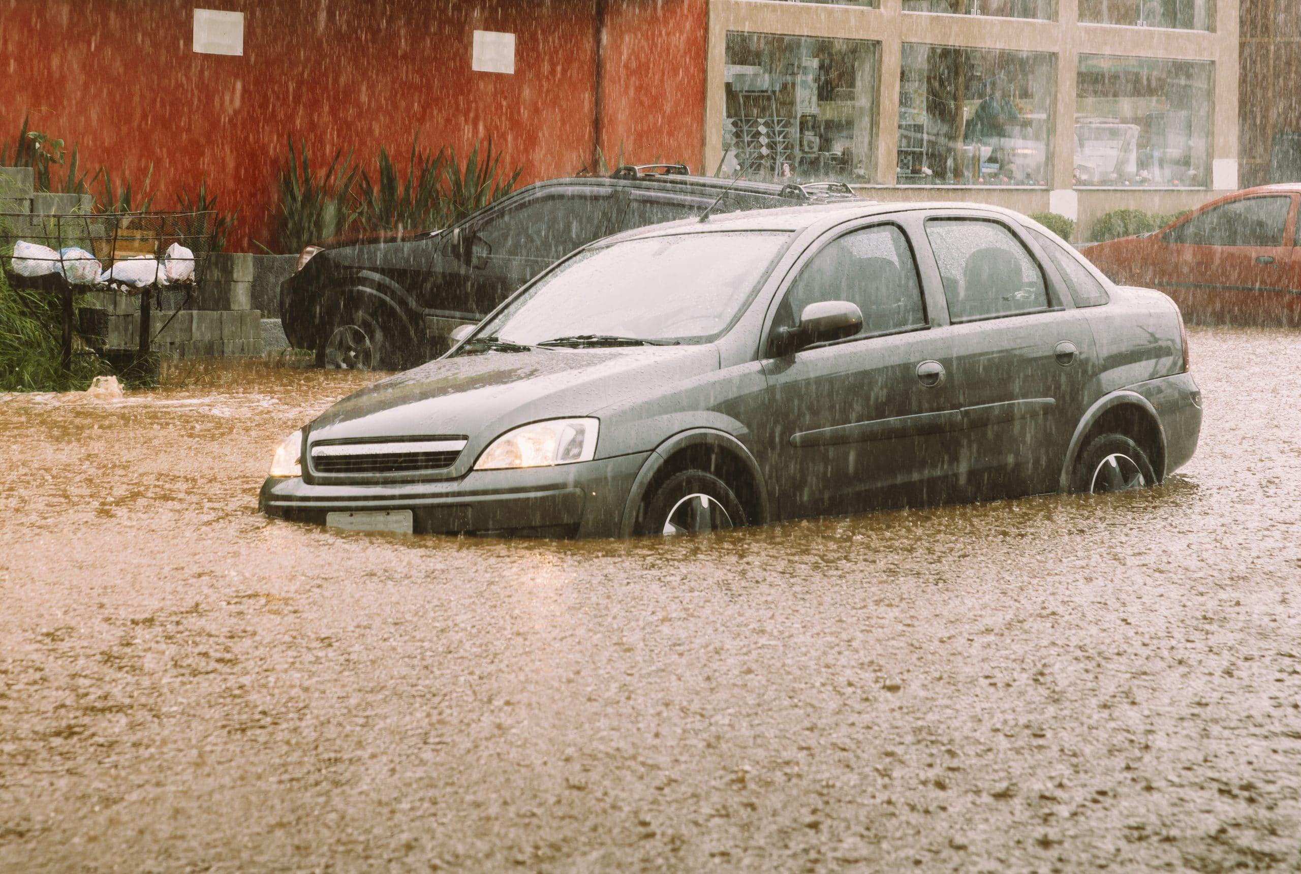 small car sinking in flood water while raining