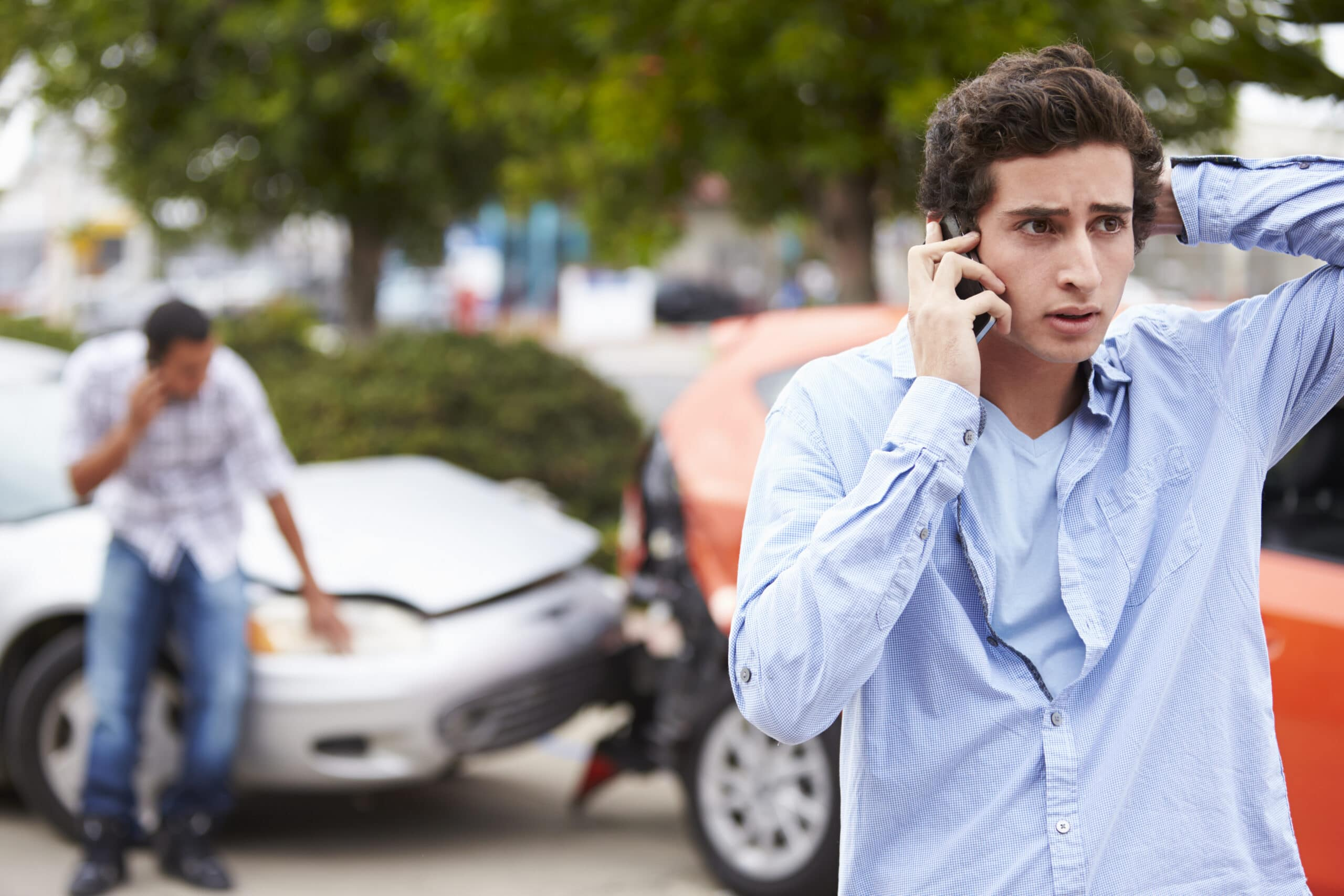 man nervously talking on the phone after car accident