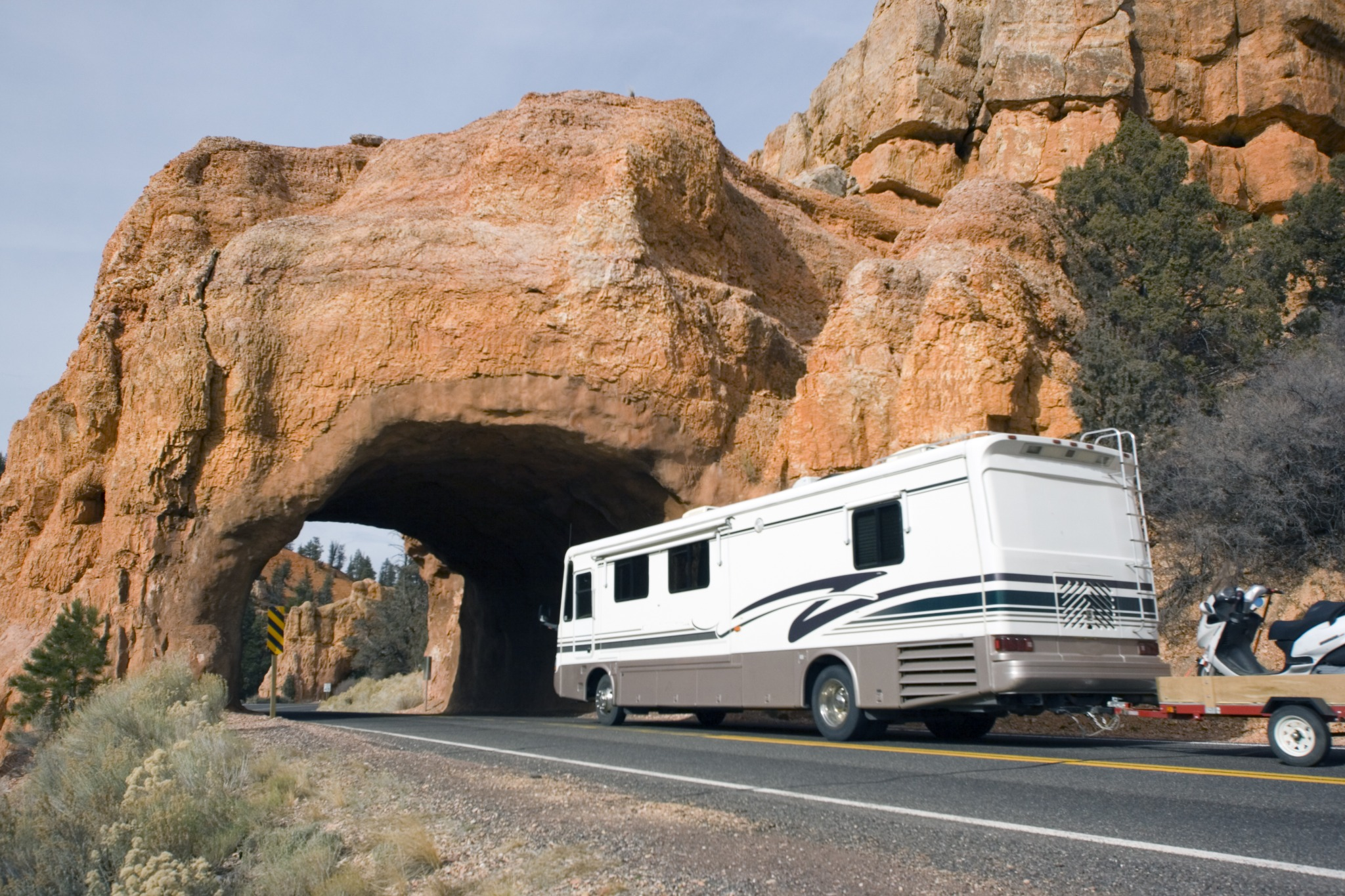A motorhome driving through a rock formation going over a road.