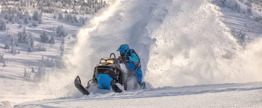 A snowmobile ride in a blue outfit riding in the snow.